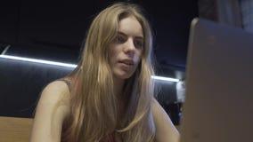 La mujer mira en el monitor del ordenador portátil almacen de metraje de vídeo