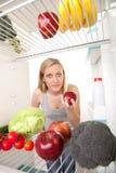 La mujer mira en el refrigerador   Foto de archivo libre de regalías