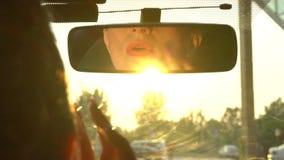 La mujer mira en espejo y se asegura de que su maquillaje está muy bien Ella toca los labios y la barbilla Sun es brillante en es almacen de metraje de vídeo