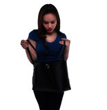 La mujer mira en su bolso Fotos de archivo libres de regalías