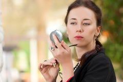 La mujer mira en un espejo del bolsillo Imagen de archivo