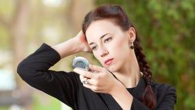 La mujer mira en un espejo del bolsillo Fotografía de archivo