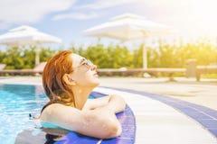 La mujer mira fuera de la piscina, colgando en la verja fotos de archivo libres de regalías