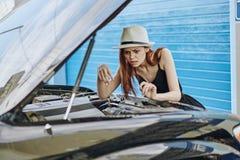 La mujer mira furtivamente debajo de la capilla del coche, servicio del coche imagen de archivo