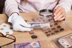La mujer mira la lira turca a través de una lupa Foto de archivo