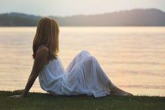 La mujer mira las aguas coloridas del lago Imagen de archivo