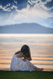 La mujer mira puesta del sol sobre el lago Fotos de archivo