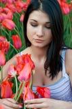 La mujer mira tulipanes. Imagen de archivo libre de regalías