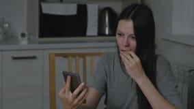 La mujer mira un vídeo en el teléfono y come una mandarina en la cocina en la noche almacen de video
