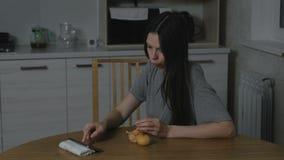 La mujer mira un vídeo en el teléfono y come una mandarina en la cocina en la noche almacen de metraje de vídeo