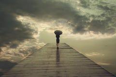 La mujer misteriosa con el paraguas cruza un puente al cielo que amenaza Foto de archivo libre de regalías