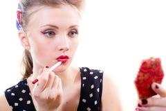 La mujer modela rubia joven atractiva atractiva dibuja el primer rojo del trazador de líneas del labio en el retrato blanco del f Imágenes de archivo libres de regalías
