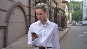 La mujer moderna joven está caminando abajo de la calle y está mirando alrededor en el d3ia, mecanografiando el mensaje en smartp metrajes