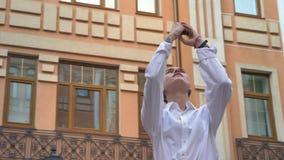 La mujer moderna joven se está colocando en el centro de la calle y la observación alrededor en d3ia, toma la foto del edificio e almacen de metraje de vídeo