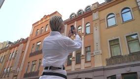 La mujer moderna joven se está colocando en el centro de la calle y la observación alrededor en d3ia, toma la foto del edificio e metrajes