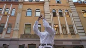 La mujer moderna se está colocando en el centro de la calle y la observación alrededor en d3ia, toma la foto del edificio en smar almacen de metraje de vídeo