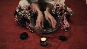 La mujer moja las manos en agua con las orquídeas almacen de video