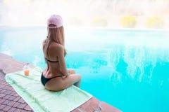 La mujer mojada joven en bikini negro y sombrero rosado, se sienta con las manos encendido fotografía de archivo libre de regalías
