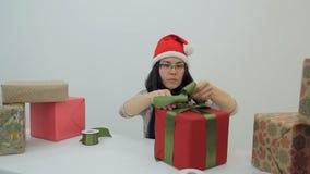 La mujer morena asiática hace el arco para adornar la caja del presente del Año Nuevo metrajes