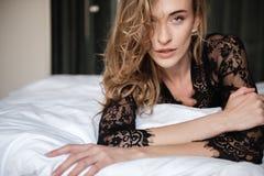 La mujer morena atractiva asombrosa miente en cama Foto de archivo libre de regalías