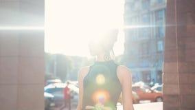 La mujer morena atractiva confiada en un vestido negro que camina abajo de la calle de la ciudad y parece atractivo derecha a metrajes