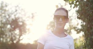 La mujer morena atractiva en gafas de sol se coloca contra la perspectiva de una puesta del sol almacen de video