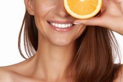 La mujer morena atractiva hermosa con la fruta cítrica en un fondo blanco, comida sana, comida sabrosa, dieta orgánica, sonríe sa Foto de archivo libre de regalías