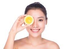 La mujer morena atractiva hermosa con la fruta cítrica en un fondo blanco, comida sana, comida sabrosa, dieta orgánica, sonríe sa Imagen de archivo