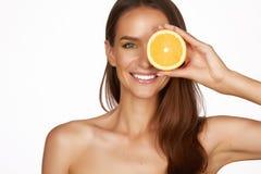 La mujer morena atractiva hermosa con la fruta cítrica en un fondo blanco, comida sana, comida sabrosa, dieta orgánica, sonríe sa Imagen de archivo libre de regalías