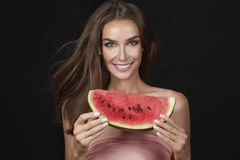 La mujer morena atractiva hermosa que come la sandía en un fondo blanco, comida sana, comida sabrosa, dieta orgánica, sonríe sano Fotografía de archivo