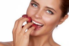 La mujer morena atractiva hermosa que sostiene cuatro bayas en sus fingeres, sonrisa atractiva y va a comer las frambuesas en un  Foto de archivo libre de regalías