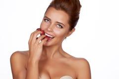 La mujer morena atractiva hermosa que sostiene cuatro bayas en sus fingeres, sonrisa atractiva y va a comer las frambuesas en un  Fotos de archivo libres de regalías
