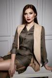 La mujer morena atractiva joven hermosa que lleva un diseño elegante del vestido de seda corto y una chaqueta de moda, los zapato imagenes de archivo