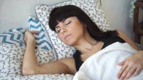La mujer morena bonita joven está durmiendo en su cama por mañana soleada, primer almacen de metraje de vídeo