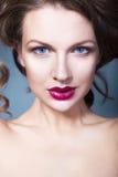 La mujer morena con creativo compone los labios rojos llenos de las sombras de ojos violetas, los ojos azules y el pelo rizado co Fotografía de archivo