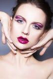 La mujer morena con creativo compone los labios rojos llenos de las sombras de ojos violetas, los ojos azules y el pelo rizado co foto de archivo libre de regalías