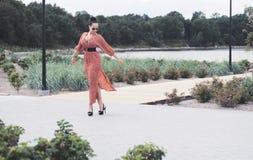 La mujer morena de moda que lleva el vestido rojo largo en gafas de sol y tacones altos camina al aire libre Imagen de archivo libre de regalías