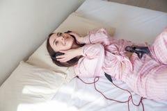 La mujer morena en pijamas que escucha la música miente en cama imagen de archivo libre de regalías