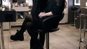 La mujer morena en traje negro con la aplicación de la cola de potro cosmética en la cara del modelo con un negro grande compone  almacen de metraje de vídeo