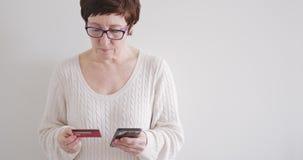 La mujer morena en vidrios hace compras en la tienda en línea con el teléfono y la tarjeta de crédito almacen de metraje de vídeo