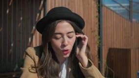 La mujer morena está llamando por smartphone y está hablando alegre, primer de la cara almacen de metraje de vídeo
