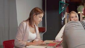 La mujer morena está trabajando con el cuaderno y está charlando con los colegas en oficina almacen de video