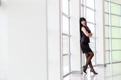 La mujer morena feliz atractiva joven vestida en un traje de negocios negro con una falda corta se está colocando cerca de la ven foto de archivo libre de regalías