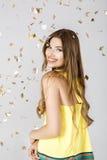 La mujer morena feliz hermosa con la sonrisa larga y el confeti del pelo se cae por todas partes Party el tiempo Fotografía de archivo libre de regalías