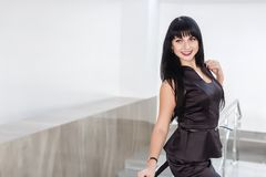 La mujer morena feliz hermosa joven vestida en un traje de negocios negro con una falda corta se está oponiendo a la pared blanca imagen de archivo