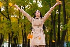 La mujer morena feliz lanza para arriba las hojas de otoño para arriba Imágenes de archivo libres de regalías
