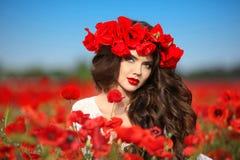 La mujer morena hermosa en amapolas coloca con las flores, attracti Fotografía de archivo