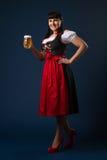 La mujer morena hermosa en Bavarian se vistió con el vidrio de cerveza Foto de archivo libre de regalías