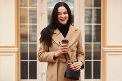 La mujer morena hermosa joven bebe el café mientras que camina alrededor de la ciudad, vistió la capa beige elegante, pequeño bol imagenes de archivo