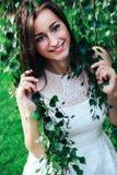 La mujer morena hermosa joven en el vestido blanco en abedul ramifica Imagen de archivo libre de regalías